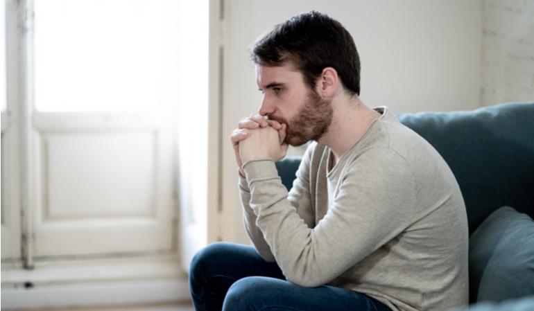 Trauriger Mann sitzt in seiner Wohnung