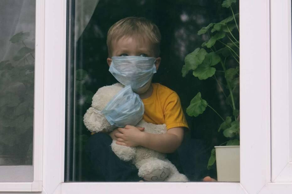 Kind mit Mundschutz hält Teddy mit Mundschutz