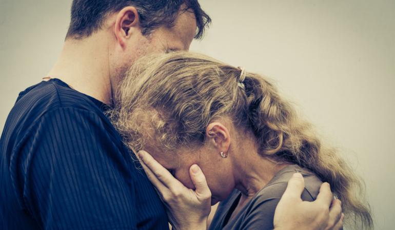 Trauriger Mann hält seine weinende Frau fest