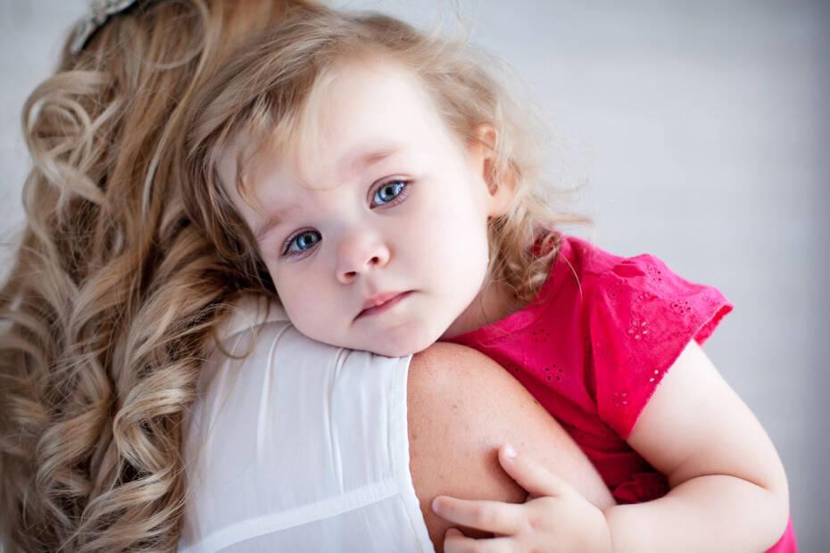 Trauriges Mädchen auf Arm von Frau