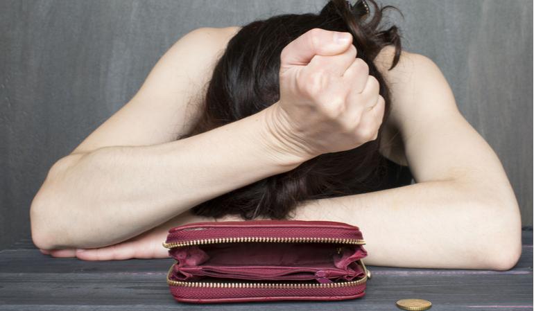 Traurige Frau sitzt vor leerem Geldbeutel
