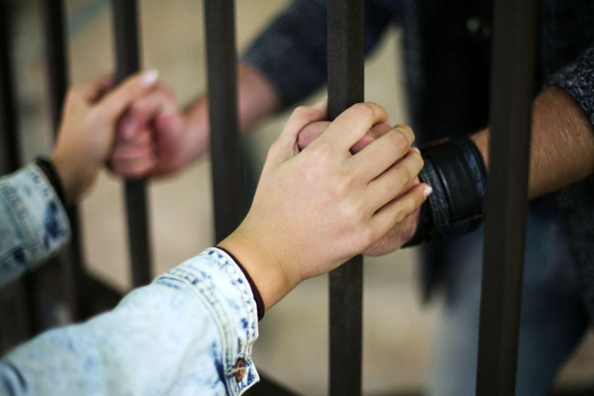 Paar hält sich die Hände durch Gitterstäbe