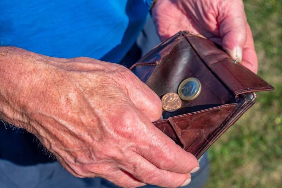 Alter Mann mit Münzen im Portemonnaie