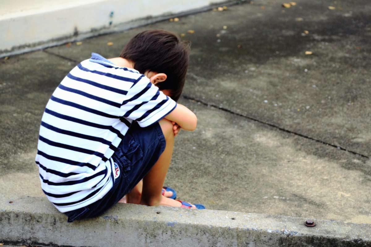 Trauriger Junge sitzt auf Treppe