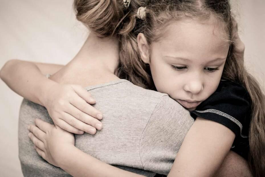 Trauriges Kind liegt in den Armen der Mutter
