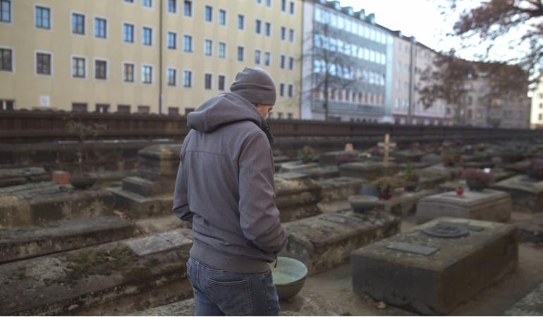 Ein Mann geht auf einem Friedhof entlang