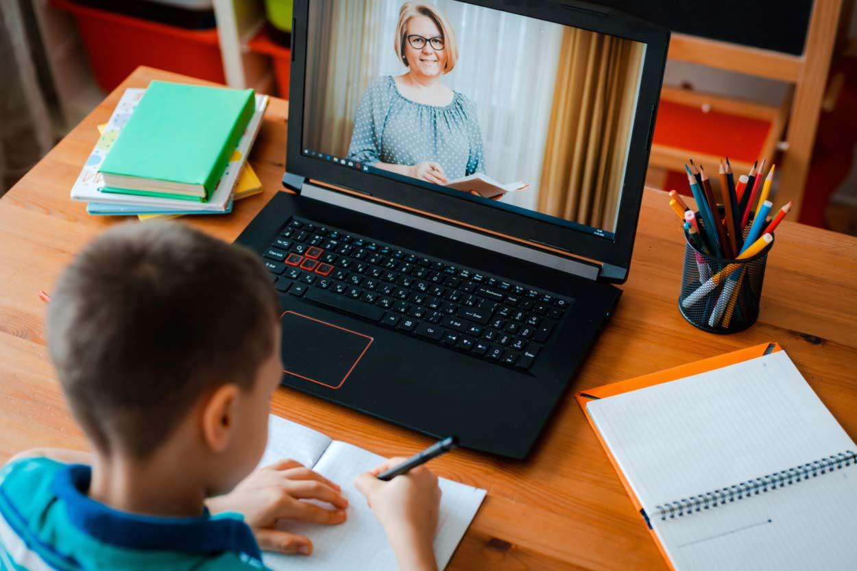 Junge sitzt vor Laptop und lernt