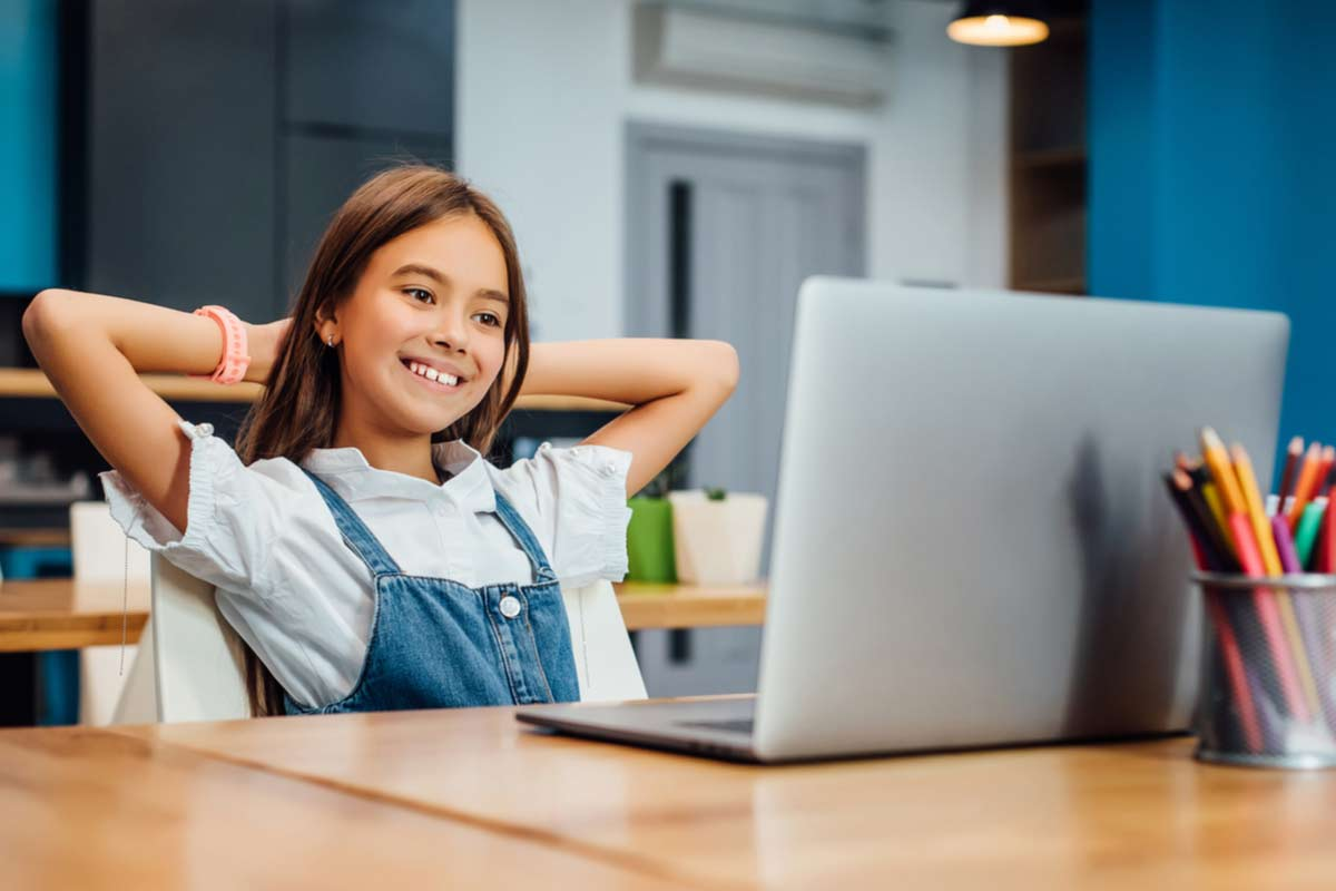 Mädchen istzt glücklich vor einem Laptop