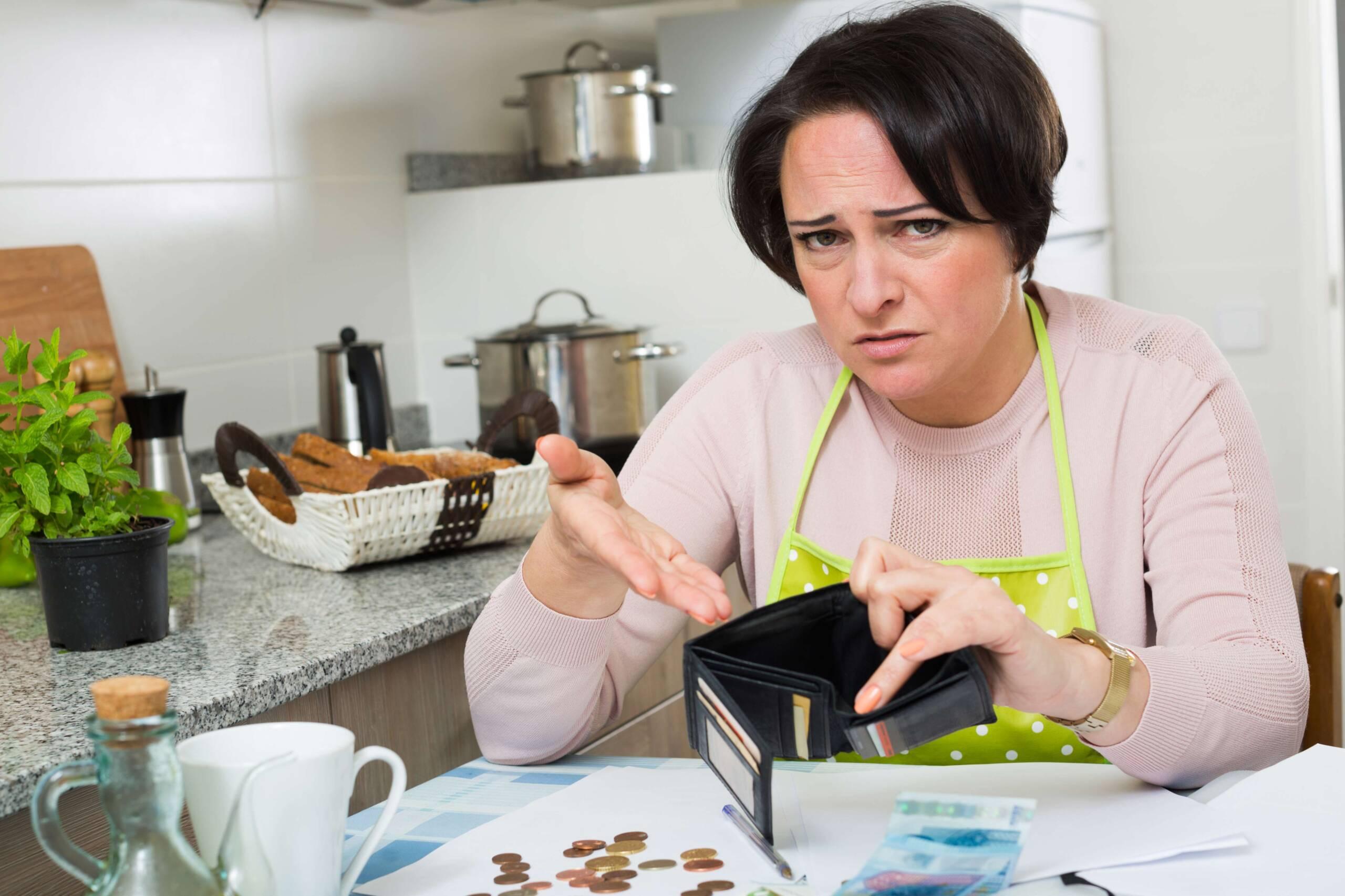 Frau sitzt verzweifelt über leerem Portemonnaie