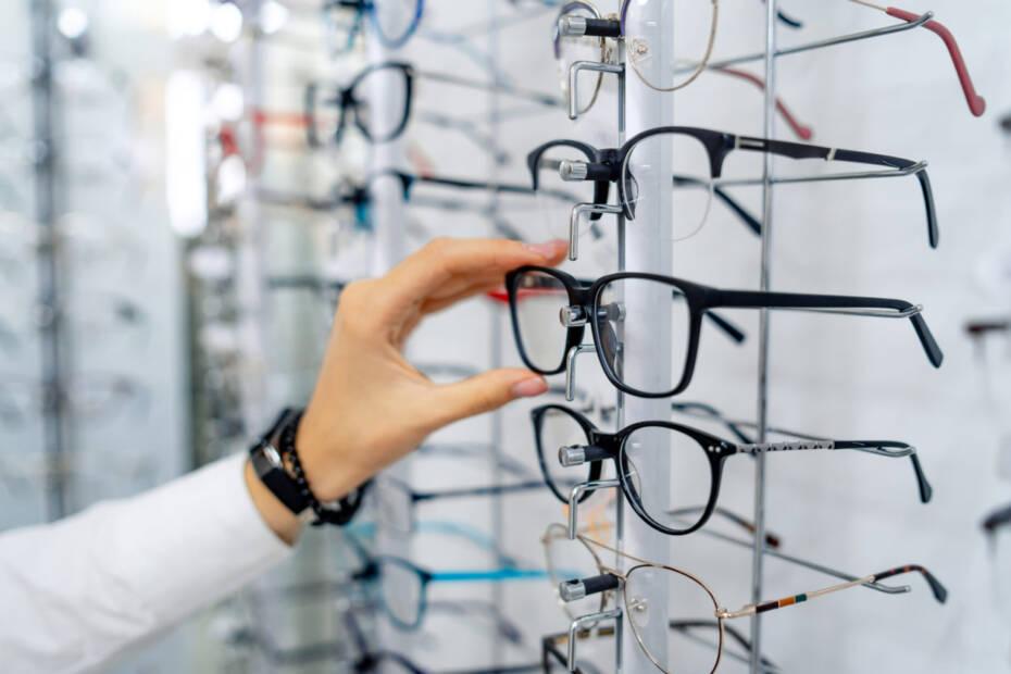 Hand greift sich eine Brille aus einem Schaukasten