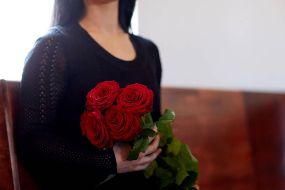 Witwe sitzt auf Kirchenbank und hält einen Strauß Rosen