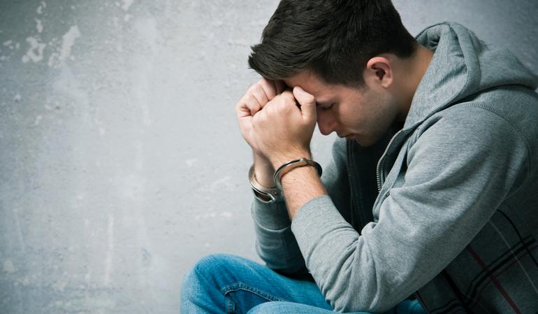 Trauriger Mann in Handschellen