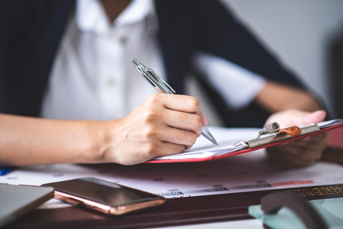 Frau prüft Dokumente mit Stift