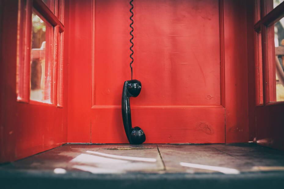 schwarzer Hörer in roter Telefonzelle