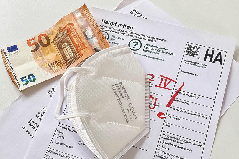 FFP2-Maske gegen Coronavirus mit 50 Euro Schein auf Hartz IV Antrag