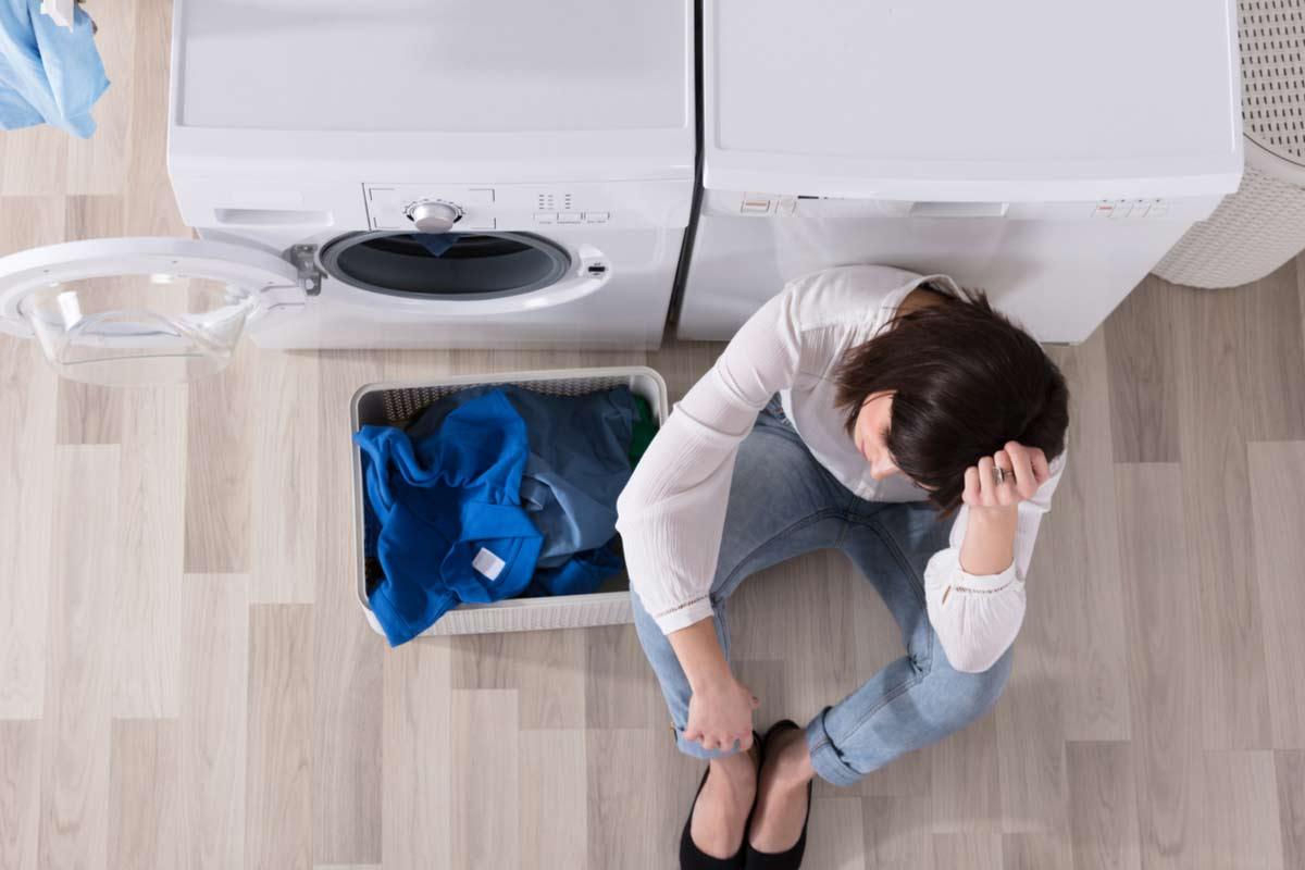 Traurige Frau sitzt vor Waschmaschine