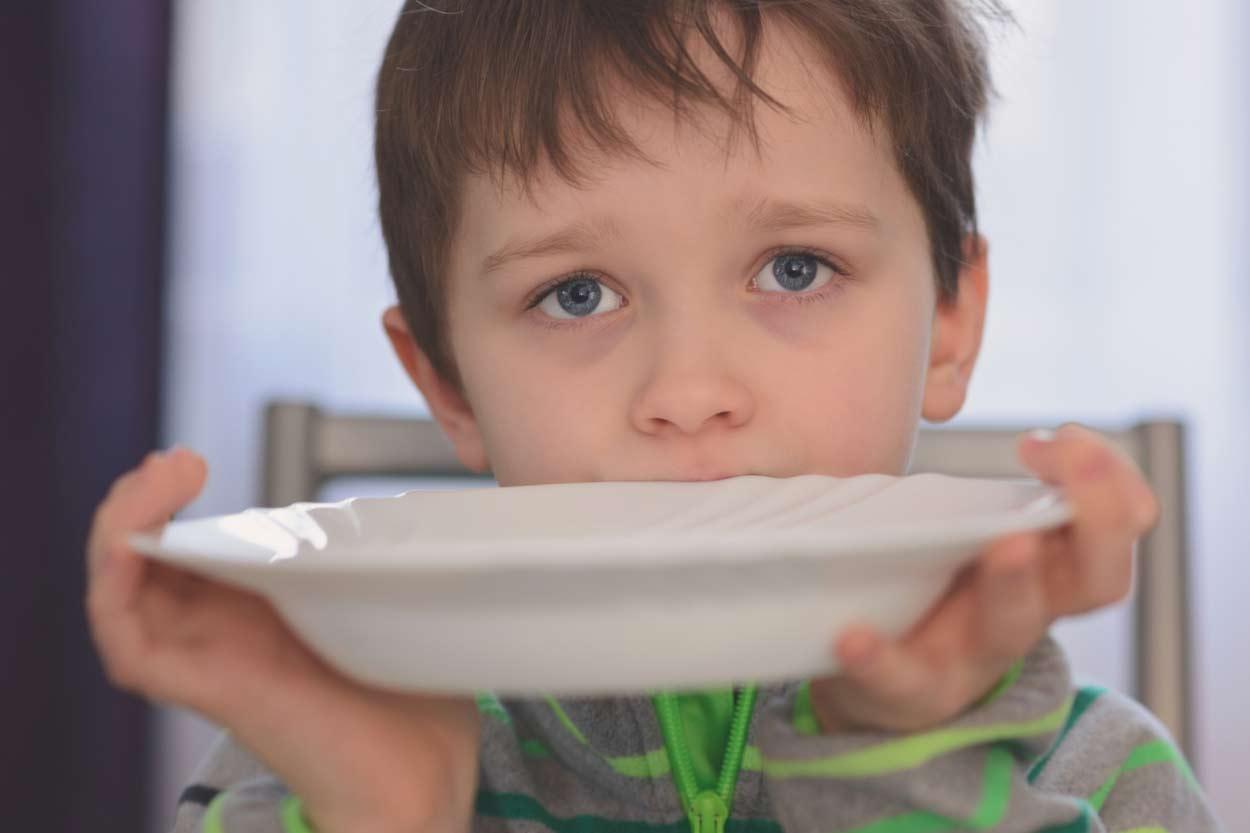 Kleiner Junge mit leerem Teller