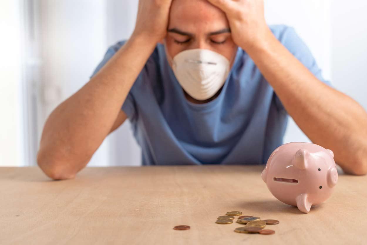 Trauriger Mann mit Gesichtsmaske vor einem leeren Sparschwein