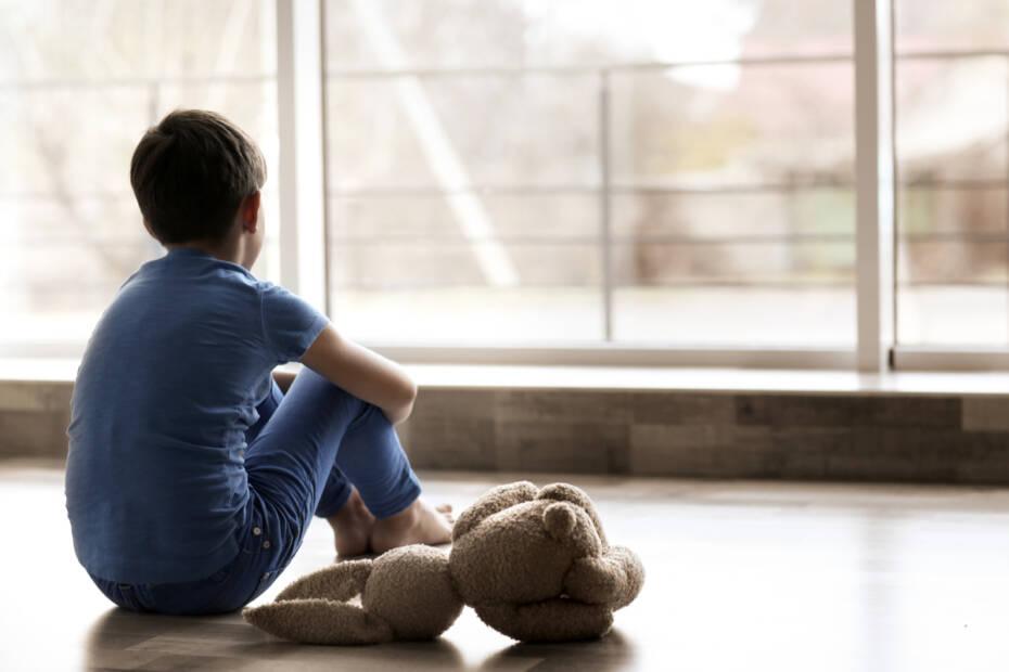 trauriger Junge sitzt mit Kuscheltier auf Boden