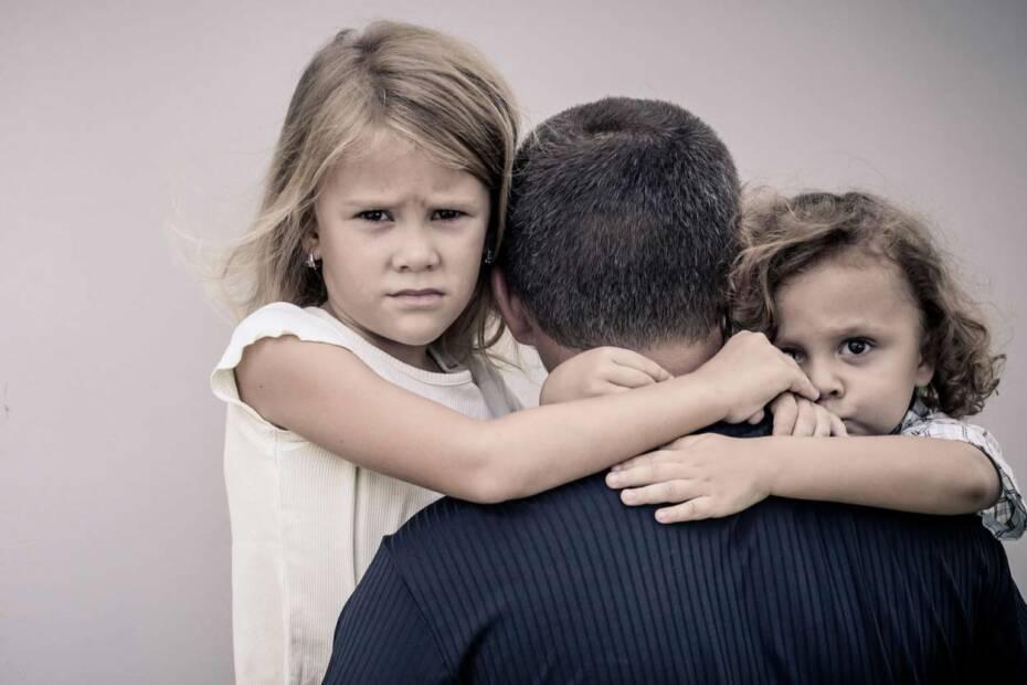 Traurige Kinder umarmen Vater