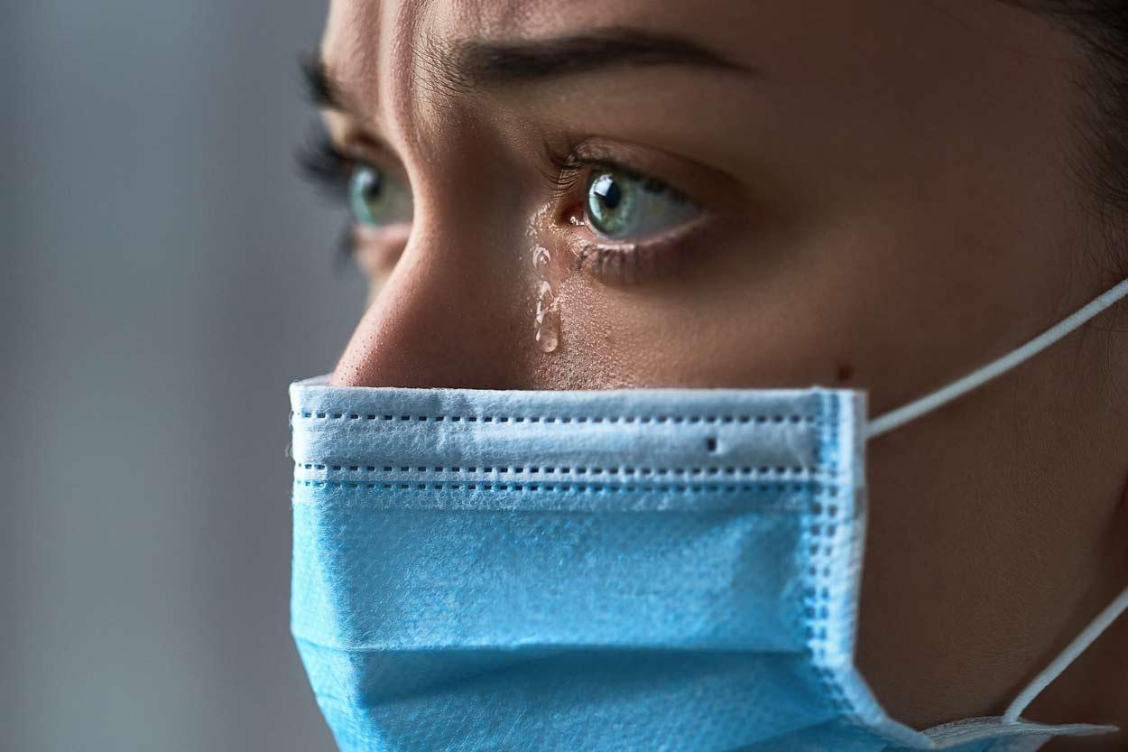 Traurige Frau mit Mundschutz