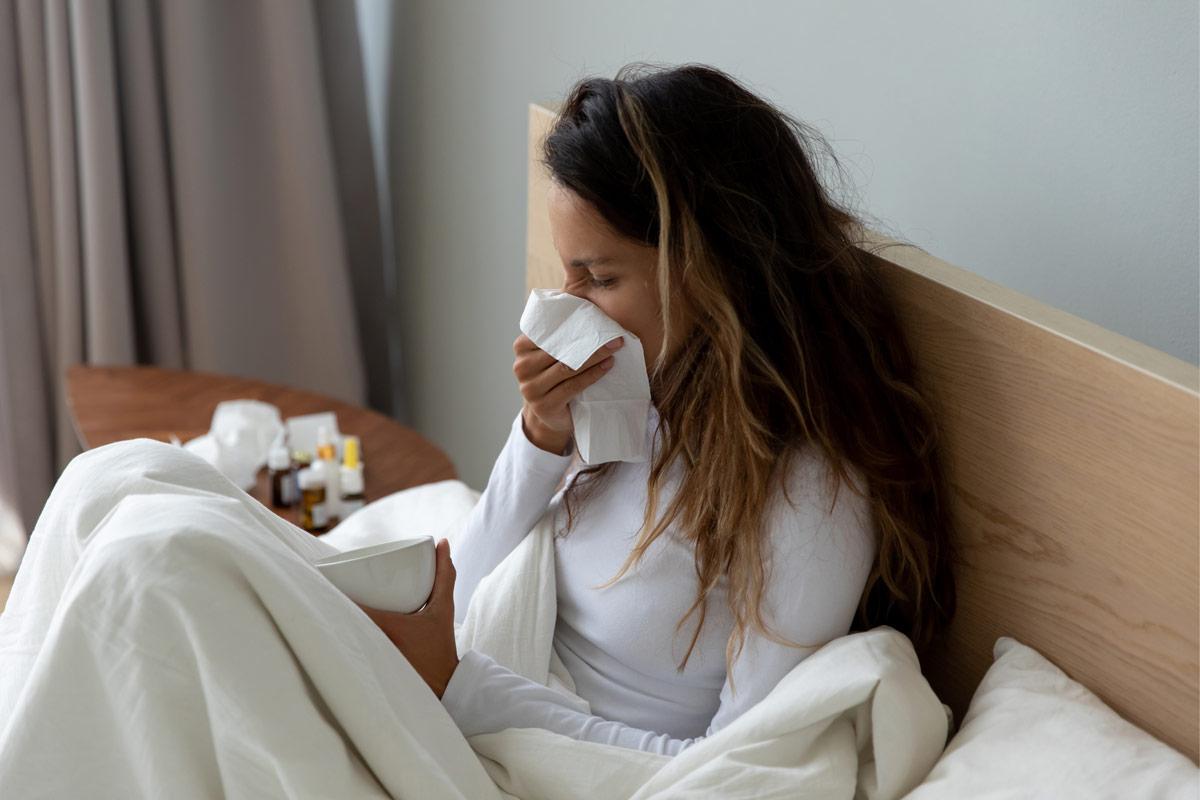 frau mit Erkältung im Bett zu Hause