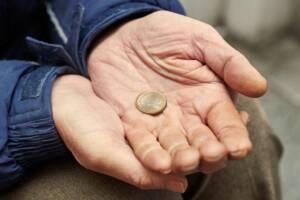 Mann hält 1 Euro in der Hand