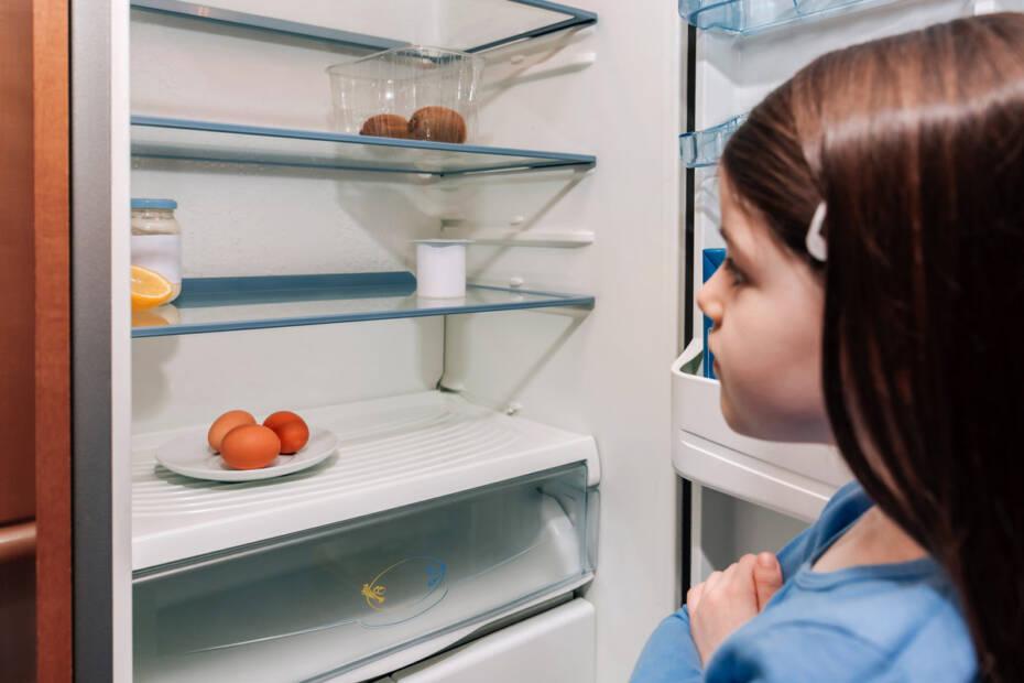 Mädchen steht in Krise vor fast leerem Kühlschrank