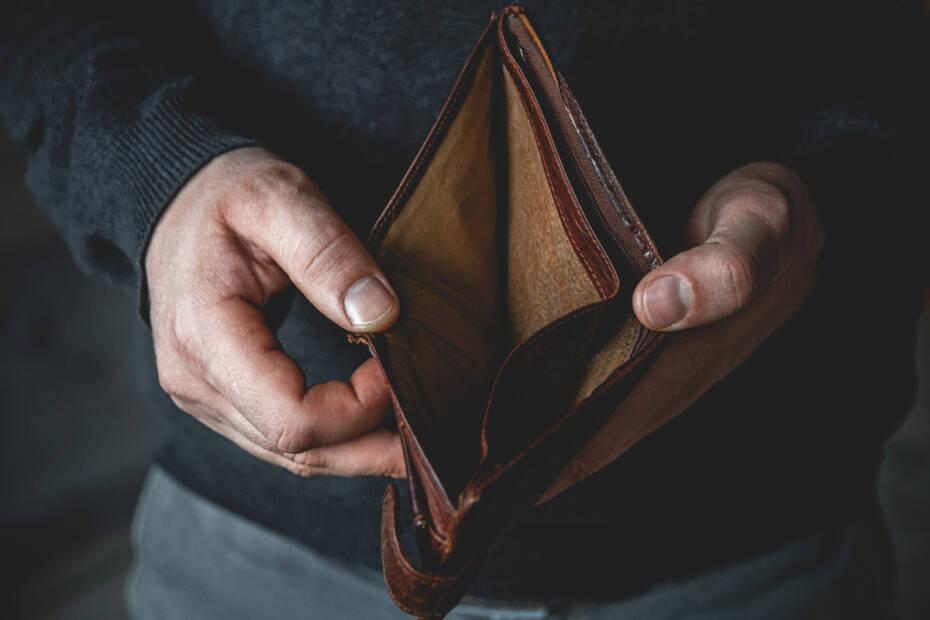 leere Geldbörse in den Händen eines jungen Mannes