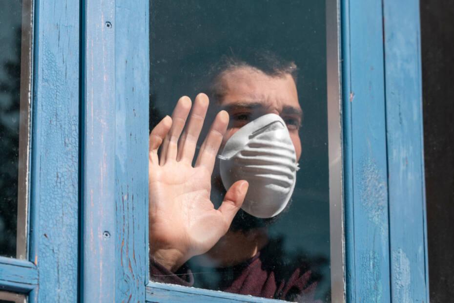 Mann mit Gesichtsmaske schaut aus einem Fenster