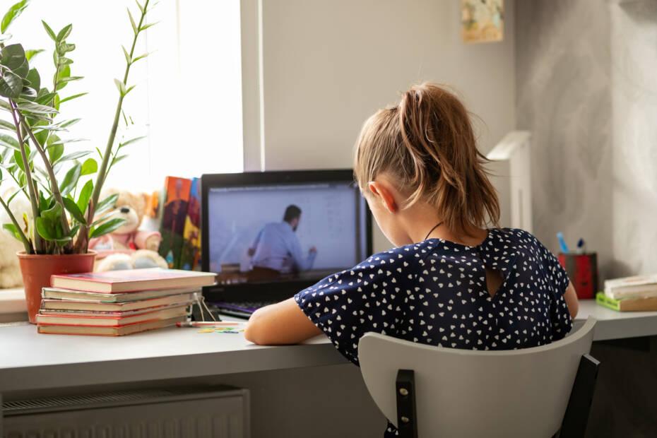 Mädchen sitzt vor Notebook beim Homeschooling