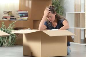 Frau sitzt traurig inmitten von Kartons