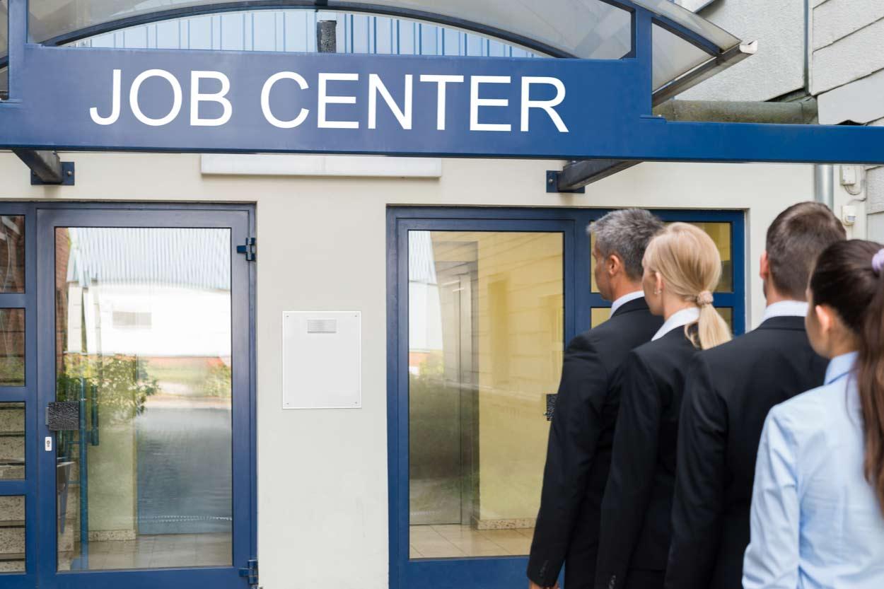 Menshcen stehen vor dem Jobcenter