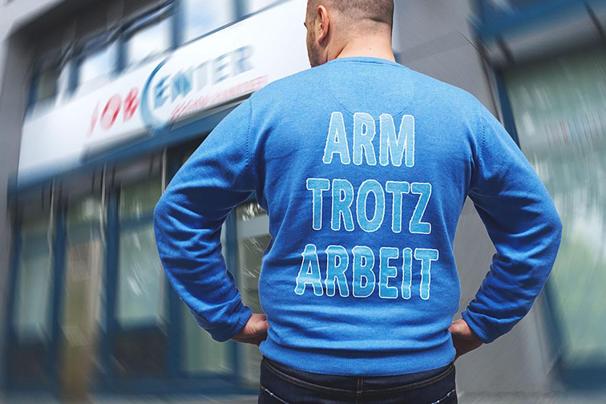 Junger Mann steht mit Aufschrift Arm trotz Arbeit vor Jobcenter