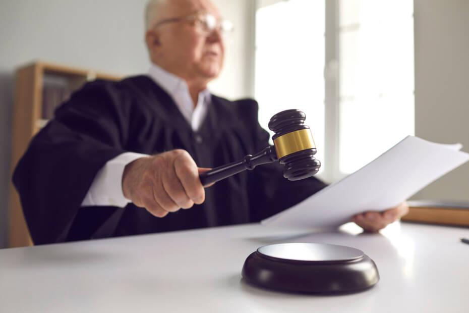 älterer Richter mit Richterhammer und Akten in der Hand