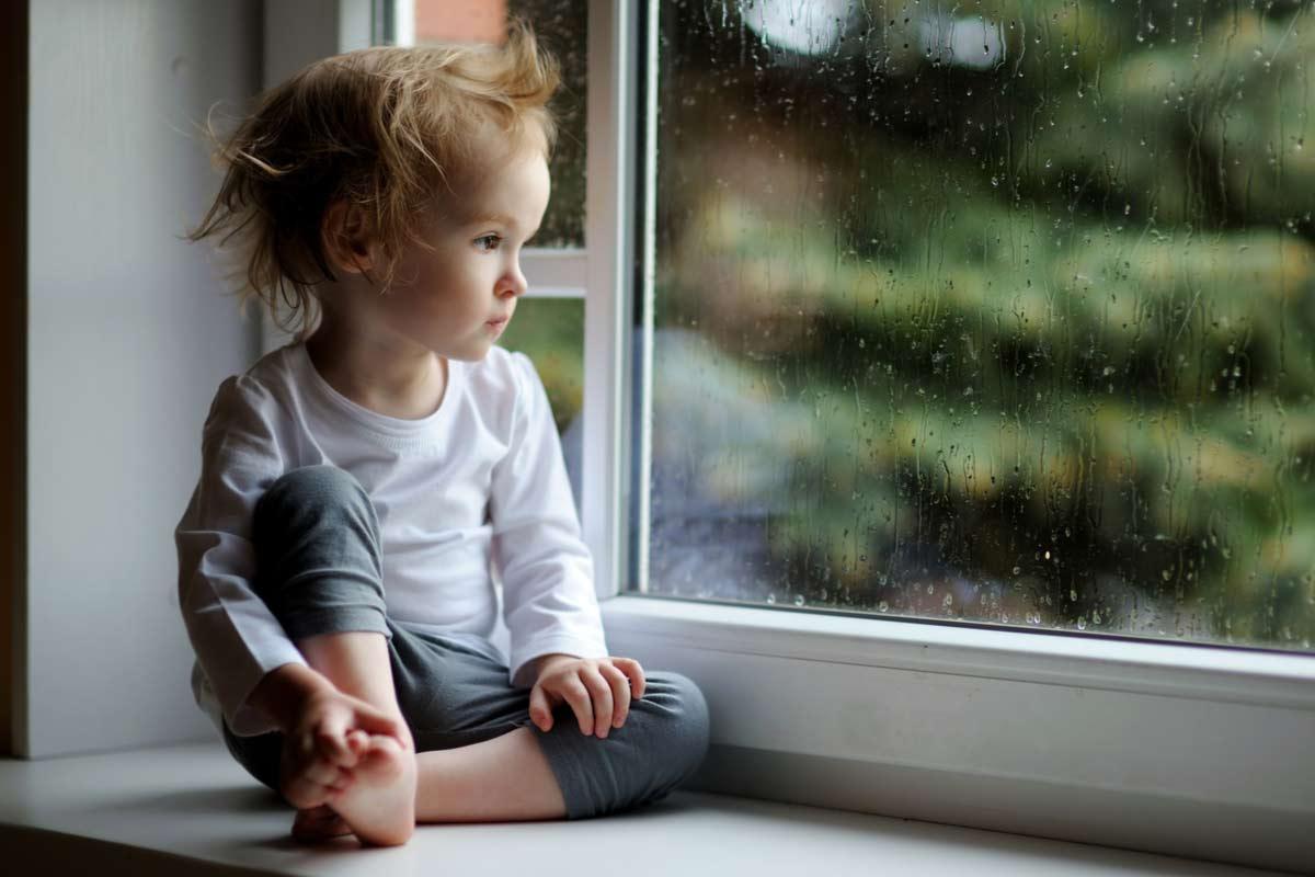 Trauriges Kleinkind schaut aus dem Fenster