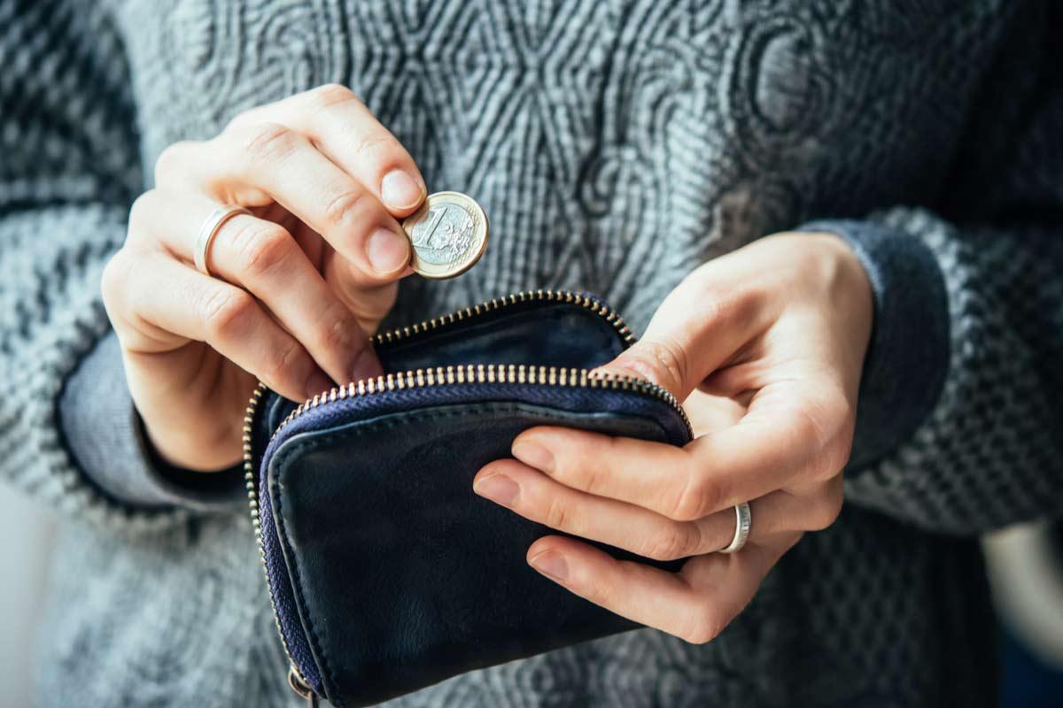 Frau steckt einen Euro in ihre Geldbörse