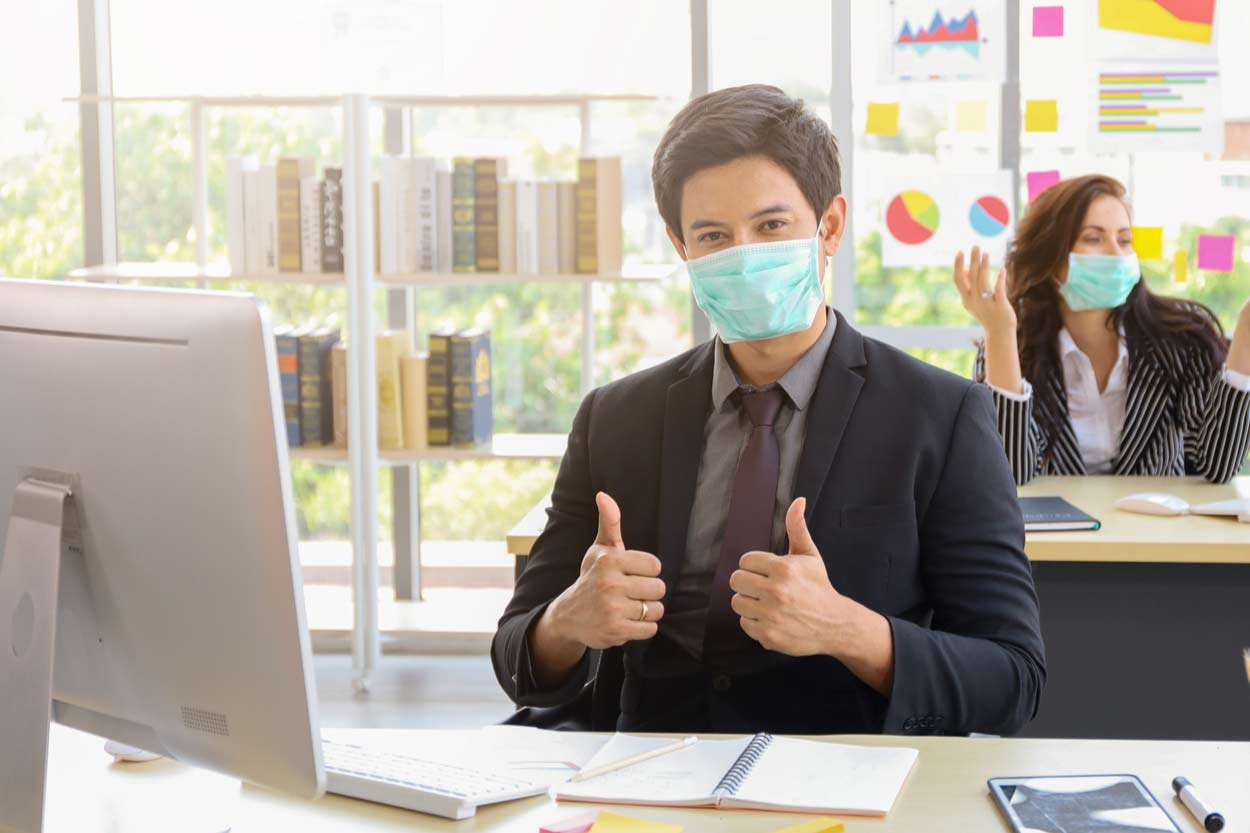 Jobcenter Mitarbeiter mit Gesichtsmaske zeigt beide Daumen nach oben