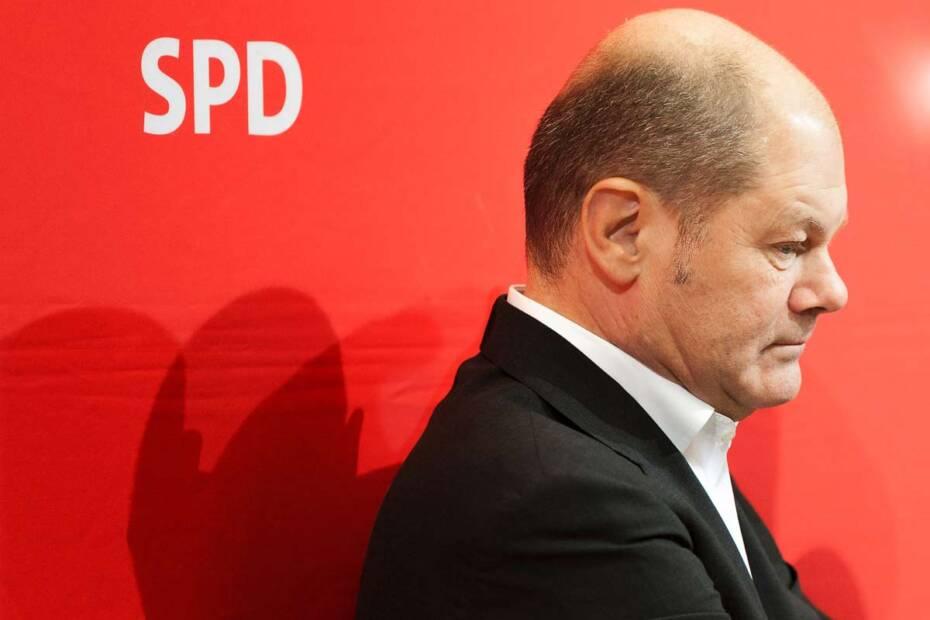 Olaf Scholz sitzt vor einer roten SPD-Wand. Lässt den Kopf hängen