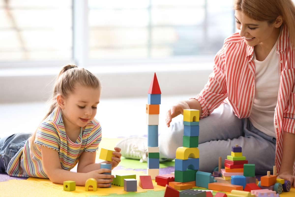 Pflegemutter spielt mit Pflegekind