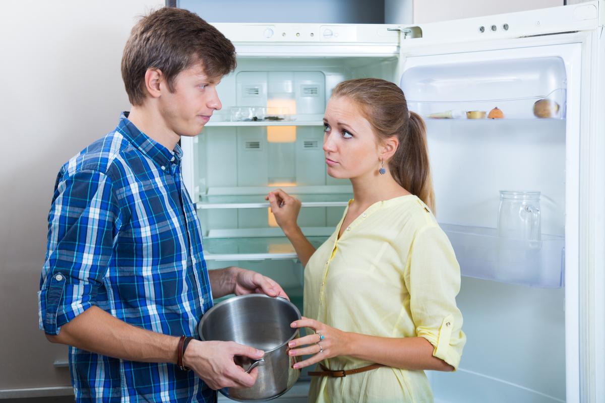 Paar steht vor fast leerem Kühlschrank