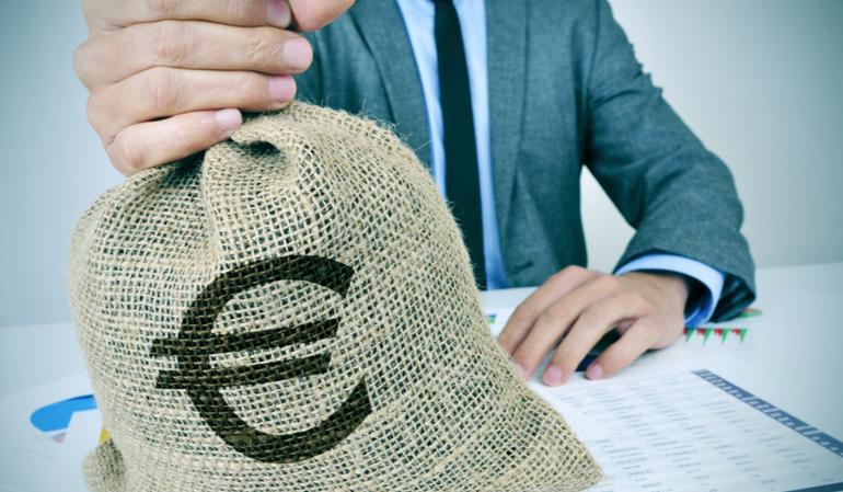 Anzugträger hält Münzsack mit Eurozeichen in der Hand