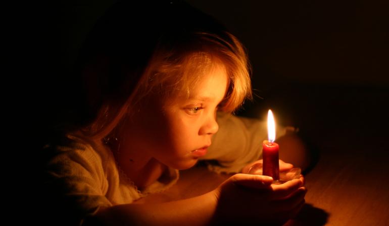 Kleines Mädchen mit einer Kerze