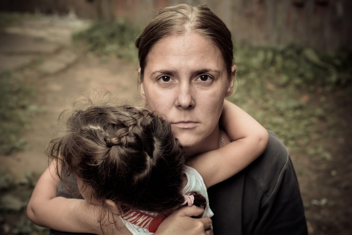 traurige Mutter mit weinendem Kind auf Arm
