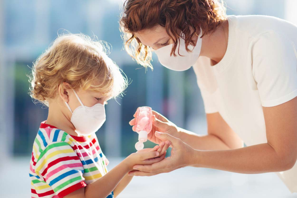 Mutter gibt ihrem Kind Desinfektionsmittel
