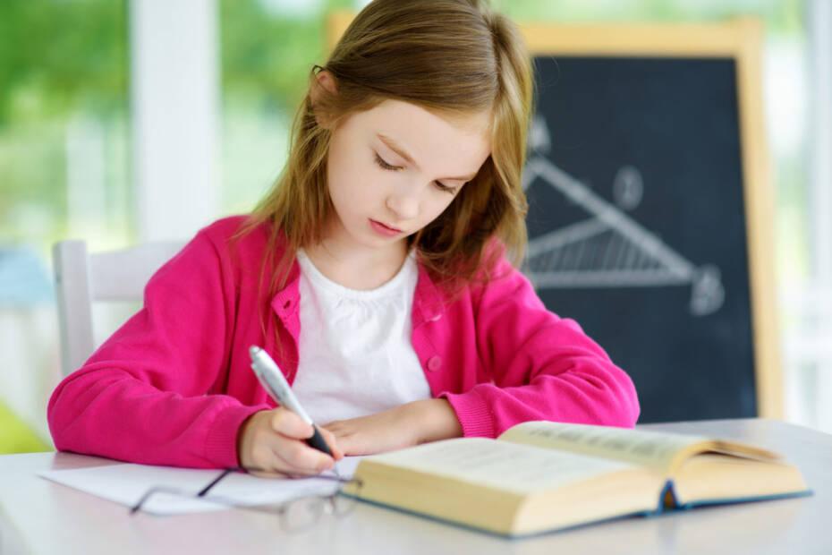 Kind sitzend am Schreibtisch