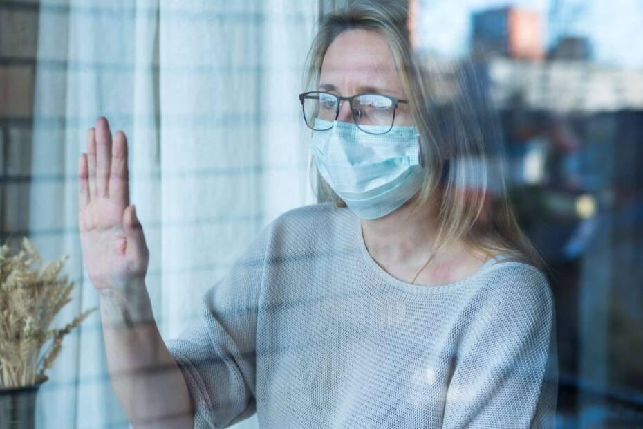 Frau mit GEsichtsamske guckt traurig aus dem Fenster
