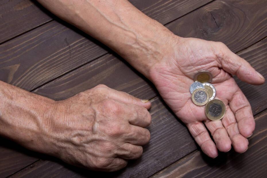 Ältere Hand hält Münzen