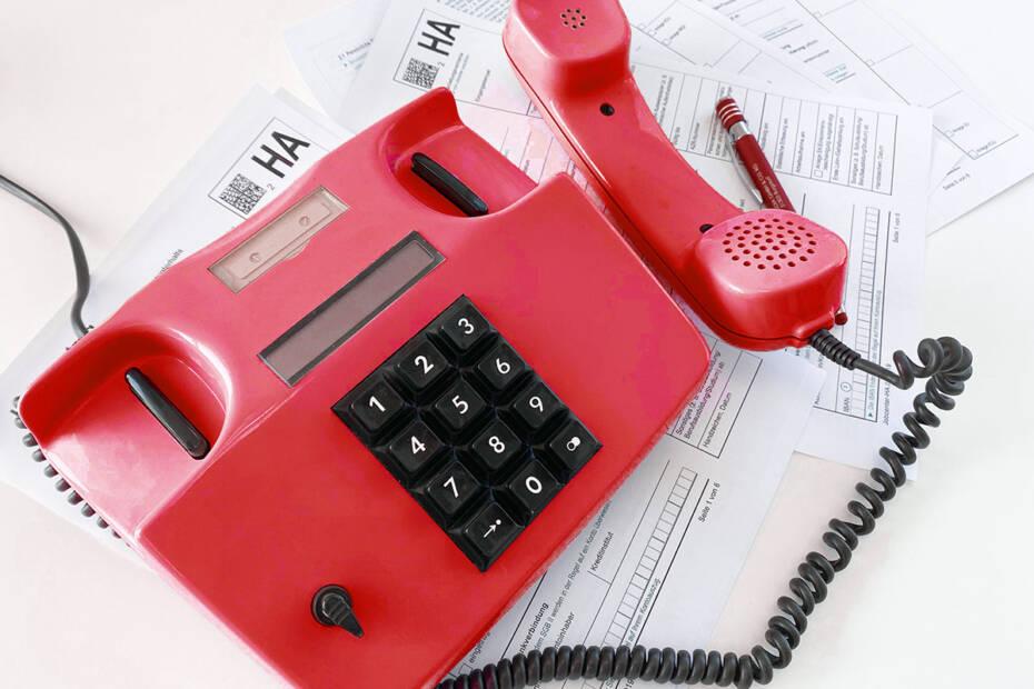 rotes Telefon auf Hartz IV Anträgen