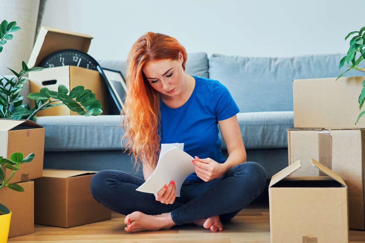 Frau liest besorgt einen Brief inmitten von Umzugskartons